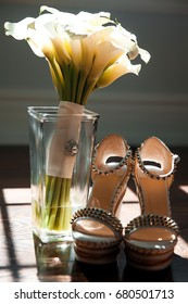 Wedding shoes and bouquet of white calla