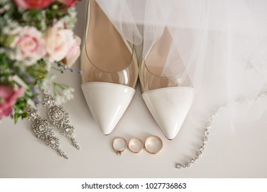 Wedding shoes for bride near one engagement ring and two wedding rings for bride and groom. Marriage concept