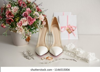 Wedding shoes for bride. White shoes on high heels near wedding rings, bidal jewelry, garter and wedding invitation. Marriage concept