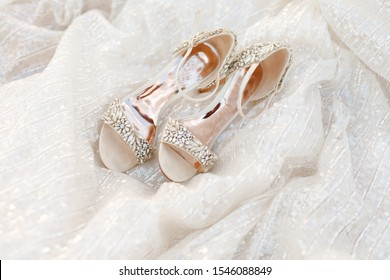 wedding shoes and wedding dress. Beautiful colorful wedding shoes for bride indoors. Beauty of bridal heel for marriage. Female couple boots for celebration