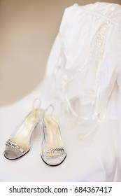 Wedding shoes and dressing gown on the white chair.
