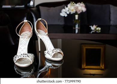 Wedding shoes with jewels on a mirror table.