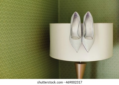 Wedding shoes on a floor lamp  on the green background  room, glamor, fashion, wedding