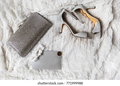 Wedding shoes, purse and garter on a gray background.