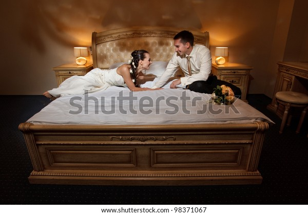 Wedding shot of bride and groom lying in a stylish bed