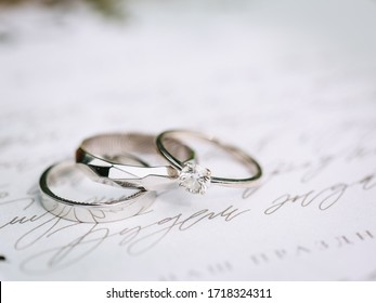 wedding silver engagement rings with fingerprint engraving inside. Lying on paper with calligraphy. nearby eucalyptus leaves