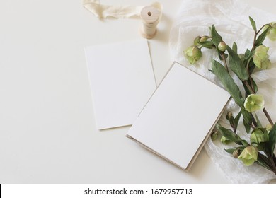 Wedding spring styled stock photo. Feminine desktop mockup scene with green hellebores flowers, silk ribbon, muslin cloth and blank paper greeting cards on white table background. Flat lay, top view.