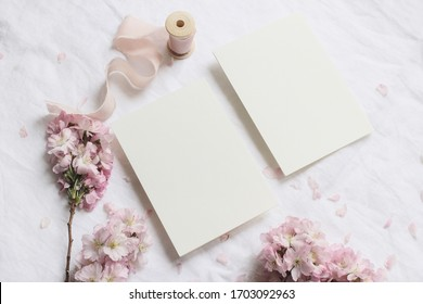 Wedding spring styled stock photo. Feminine desktop mockup scene with pink blossoming Japanese cherry tree branches and blank paper greeting cards on white linen table background. Flat lay, top view.
