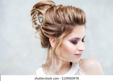 Wedding style. Beautiful young bride with luxury wedding hairstyle on light background.