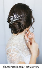 Wedding stylish hairstyle with accessories. Elegant brunette bride back with collected up do hair.