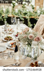 Wedding table decor in a restaurant. Decorated with pink rose and white gypsophilia flowers. Food and cold appetizers on the table