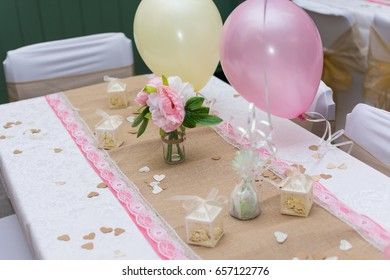 wedding table decorated with flowers and wedding favours with two balloons.