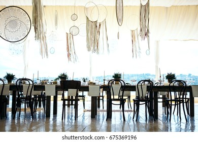 Wedding table decorated in the style boho. Decorated with details, flower arrangement in vases,  candles  and dream catchers