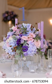 Wedding table decoration with violet, blue, pink flowers and greenery