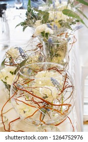 Wedding table decoration with white hortensias, carnations and muscari flowers in glass ball.