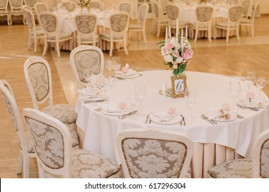 Wedding table decoration with the white and pink roses, carnations and candles