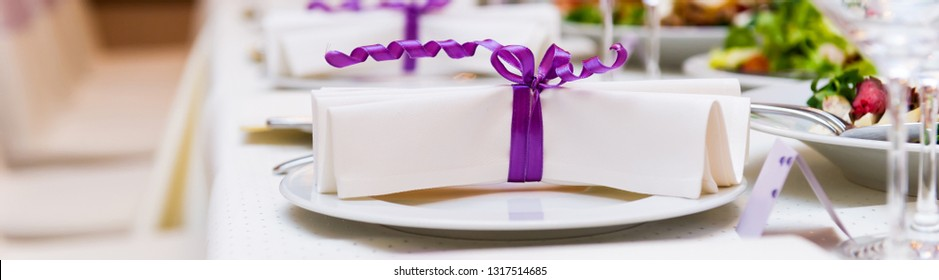 Wedding table decorations, close up white folded napkin with purple violet bows on plates in row, birthday banquet, life event, restaurant business, catering, service conceptual image horizontal view