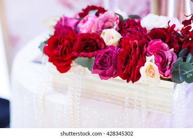 Wedding table decorations. Red roses in a basket sitting on a table.