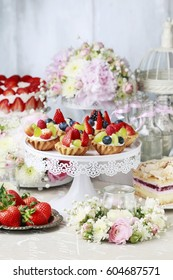 Wedding table with delicious sweets and beautiful flower decorations.