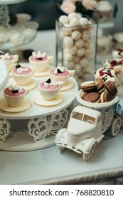 The wedding table dessert full of delicious chocolate cups with marshmallows and car toy with chocolate macarons. Vertical shot.