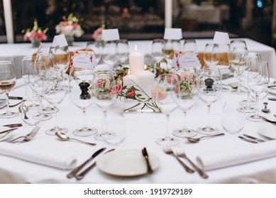 Mesa de matrimonio en el restaurante decorado con velas blancas y flores.