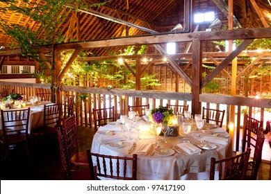 wedding table set for fine dining in a barn