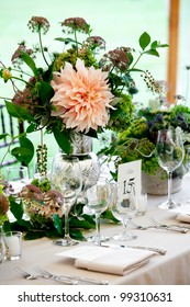 a wedding table set for fine dining with a pretty flower centerpiece
