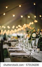 Wedding table setting with bistro lights.