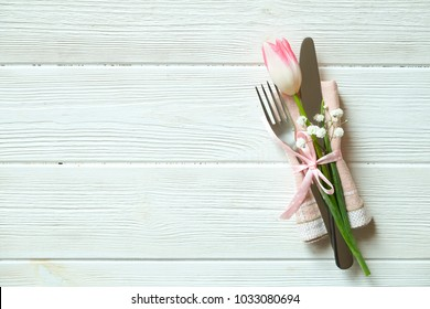 Wedding table setting composition with fork & knife silverware, pink tulip tied with pink ribbon on white wooden texture table background. Happy easter greeting card. Close up, top view, copy space.