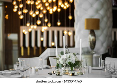 Wedding table setting is decorated with fresh flowers and white candles. Wedding floristry. Bouquet with roses, hydrangea and eustoma. On the background blur are burning garlands with light bulbs