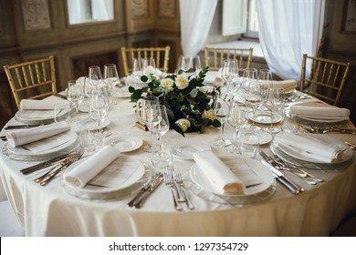 Wedding table setting. White plates and napkins lie on the dinner table decorated with greenery and golden roses
