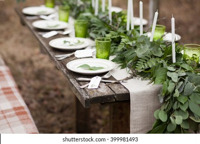 Wedding table setting with white plates and green glasses decorated with white candles, green leaves and eucalyptus and linen tablecloth outdoors