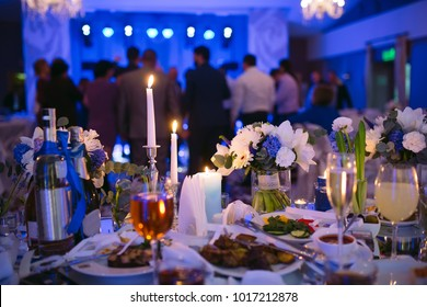 Wedding table settings in the restaurant. People dancing in the background of the Bridal table.