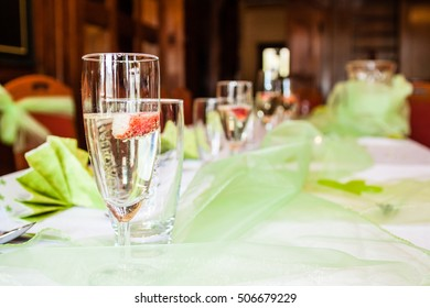 Wedding table with white green colors and glass champage