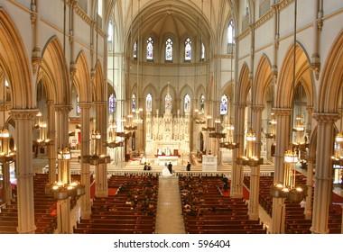 A wedding takes place inside an ornate church.