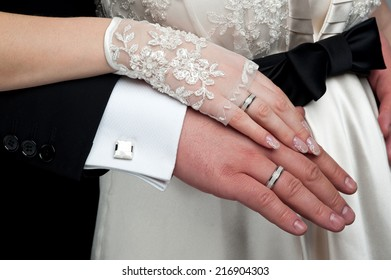 Wedding theme. Just married couple's hands together. Lace gloves, rings, cufflinks.