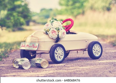 wedding toy car with stringed cans and Bouquet