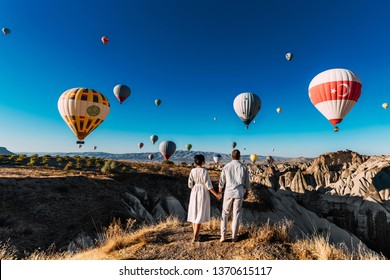 Wedding travel. Honeymoon trip. Couple in love among balloons. A guy proposes to a girl. Couple in love in Cappadocia. Couple in Turkey.  Man and woman traveling. Festival of balloons. Follow me