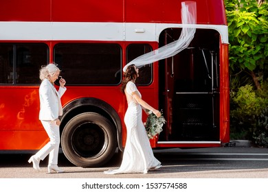 Wedding veil is flying on the wind and lesbian brides are smiling in front of red double decker bus