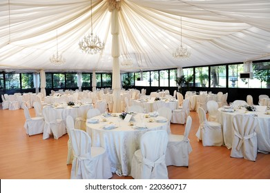 Wedding venue under a marquee with decorated tables and chairs draped in white linen around a central pole supporting the canvas