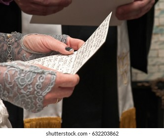 Wedding Vows A bride holds a paper on which her wedding vows are written by hand. Her arms and part of her hands are covered in gray lace. The minister stands in the background. His stole is visible.