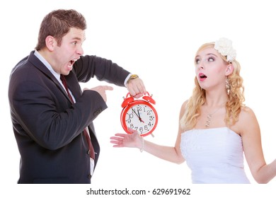 Wedding, waiting for celebration and proposal, negative bad relationship concept. Groom holding bid red clock yelling at his birde future wife in white dress.