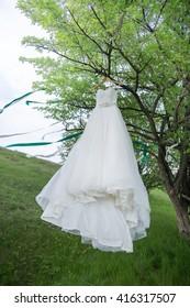 The wedding white dress hangs on a tree