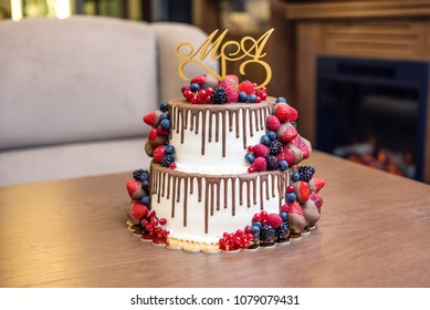Wedding white two tier cake decorated with chocolate and berries in the glaze. The concept of festive desserts