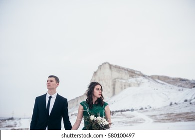 Wedding in the winter on the nature near the cliff. Bride in green dress. Wedding concept