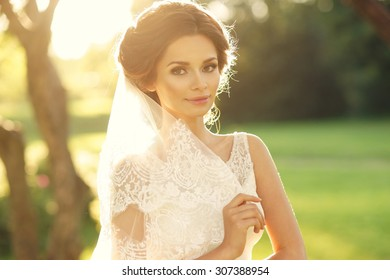 Wedding. Young beautiful bride with hairstyle and makeup posing in white dress and veil. Soft sunset light summer portrait. Girl looking in camera