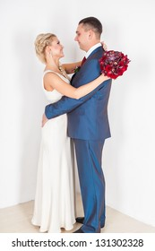 Wedding: young couple in love bride and groom hugging each other holding a bouquet of flowers
