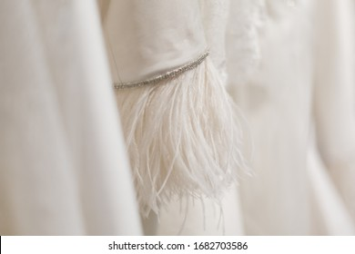 Weddingdress details from dresses hanging on a rack in a wedding dress shop
