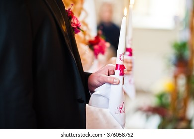 Weddings candle at hands of newlyweds