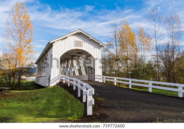 Weddle Wooden Covered Bridge in Sweet Home Oregon in Autumn with Yellow, Golden Trees and Blue Sky and Clouds.